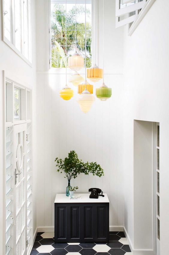 A cluster of sherbet-colored art deco pendant lights highlight the high ceiling, while adding subtle color and casual elegance to the entry