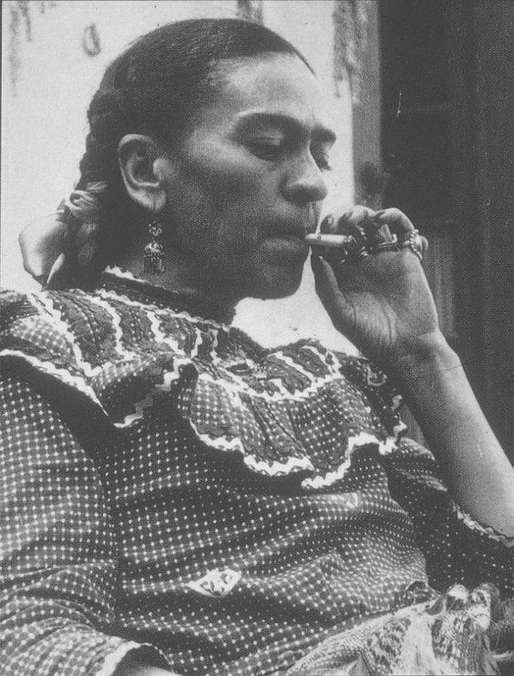 Frida Kahlo smoking a cigarette | smoking | black & white photography | iconic | artist | troubled | creative | drawback | puff | inhale | exhale | check blouse |