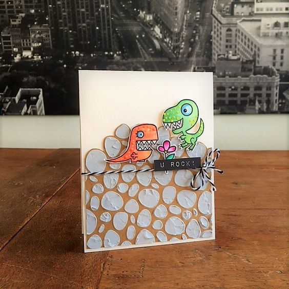 "Dinosaurs Rock Card. Stamps: Paper Smooches (""Cutesaurus"", ""Spring Fling""), Altenew (""Label Love""); Stencil: Echo Park (""Rocks""); embossing paste, pearl markers, watercolours, twine.:"
