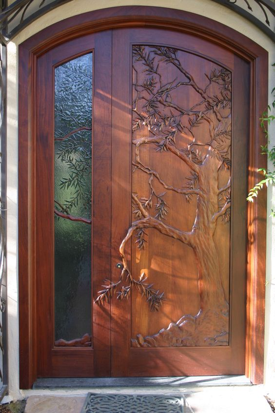 Hand carved door, olive tree carved in wood and theme continued in art glass side lite.:
