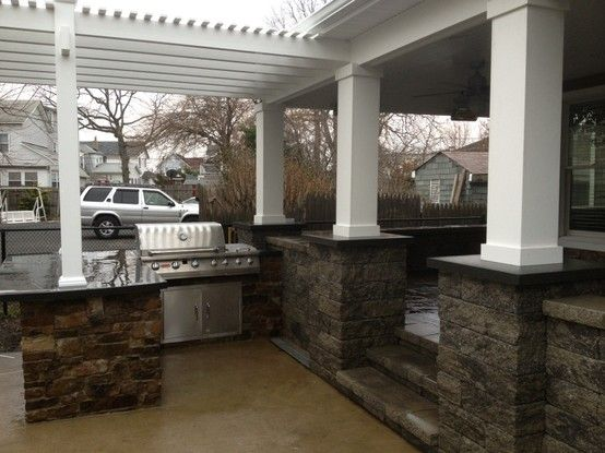 A custom natural stone out door kitchen with polished bluestone countertops.