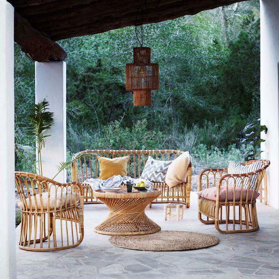 Salon de jardin en rotin sur une terrasse pavée