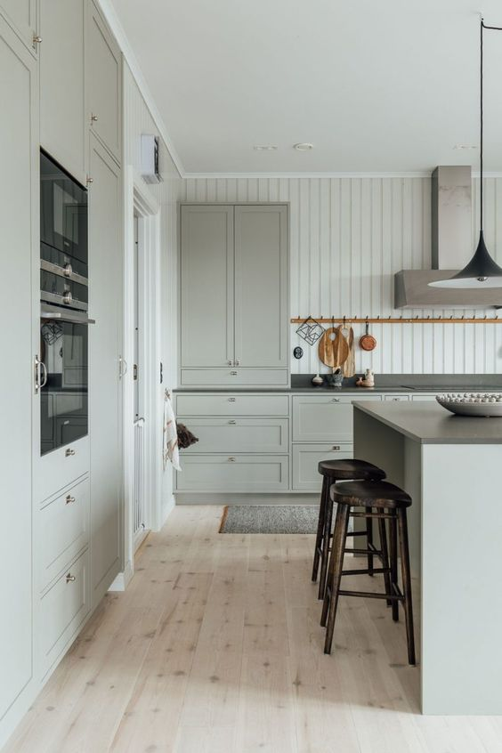 Shaker style kitchen with tongue and groove backsplash + light pickled pine floors + dark wood barstools backless + sage green cabinetry and walls + light green cabinets in the kitchen | Nordic Design