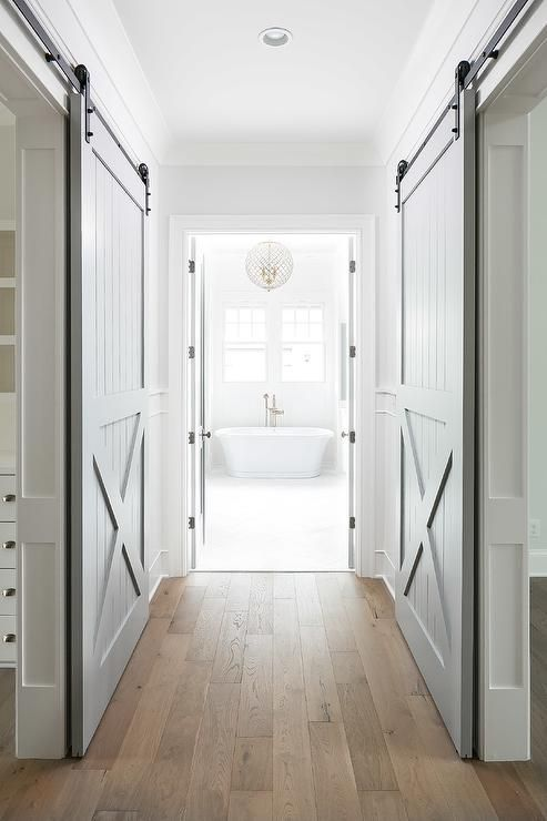 Gray Barn Doors On Rails Conceal His And Her Closets Facing Each Other With A Wood Floor Hallway In Bet Interior Barn Doors Hamptons House Hamptons Style Homes