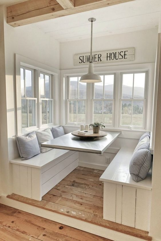 Charming built-in booths with rustic wood, white farmhouse pendant light, and Summer House sign in kitchen. #cottagestyle #banquette #breakfastroom