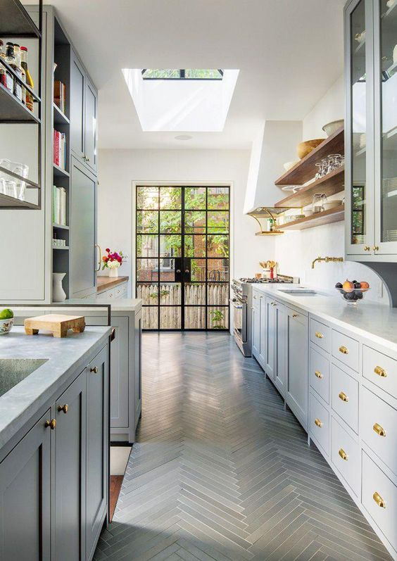 Bright galley style kitchen with gray herringbone floors, brass hardware, skylight, and floating shelves.