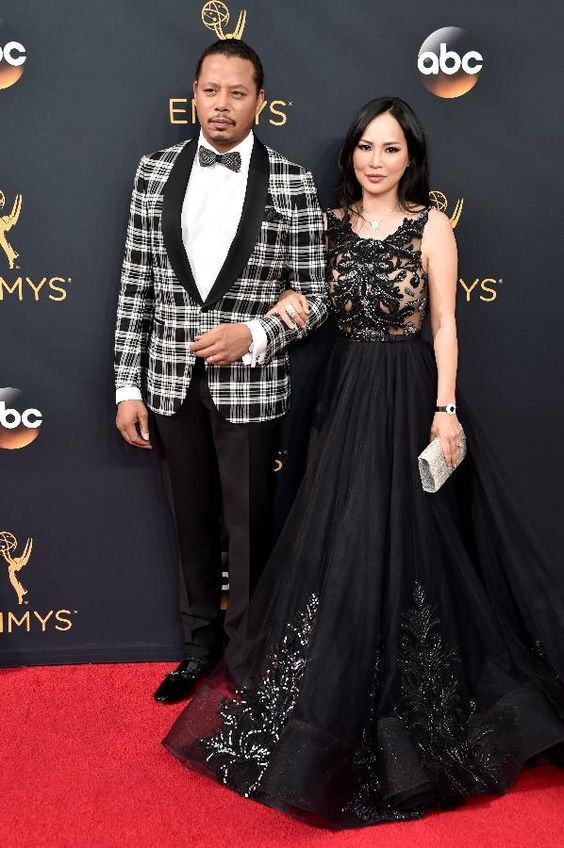 Sporting an Isaia tuxedo, Empire's Terrence Howard and his wife Mira Pak strike a pose on the red carpet at the 68th Annual Primetime Emmy Awards.