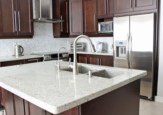 Deep cherry adds to the elegance of these white countertops. It's even more apparent with the framed doors and bold hardware.