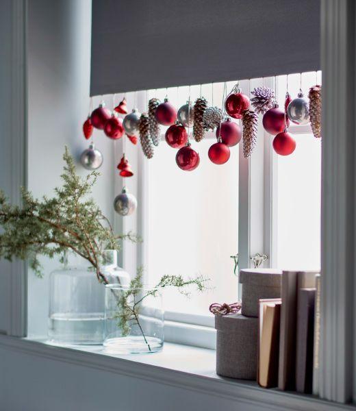 Numa janela, a parte de baixo de um cortinado branco está decorado com enfeites IKEA: