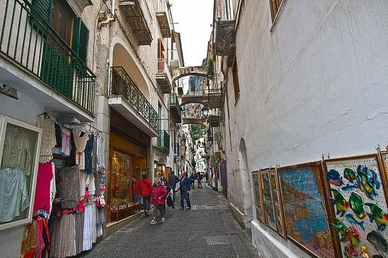Window shopping along cobblestone streets of Amalfi, Italy, where overhead bridges span the narrow lanes and limestone cliffs tower in the background
