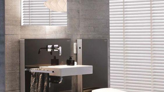 """Ce WC lavant, équipé d'une douchette à jet perlé très doux, est monté sur un panneau de verre qui dissimule le réservoir et le châssis métallique. Le panneau existe en diverses couleurs et pour lavabo. WC """"AquaClean Sela"""", 2 846 euros et panneau """"Monolith"""", 595 euros (hors cuvette) et 1 650 euros (hors lavabo), le tout Geberit."""