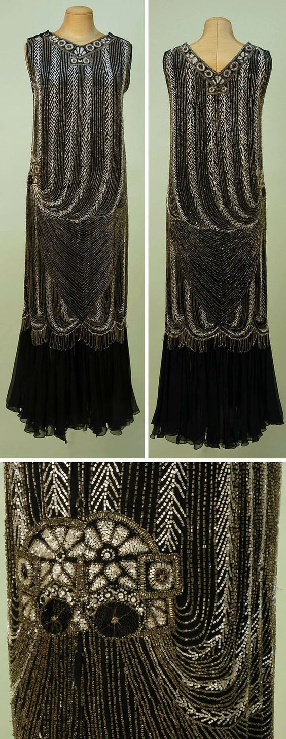 Evening gown ca. 1920s. Black silk georgette column with V-neck & V-back in chevron/stripe swag pattern of crystal, white, & rhinestone beading. Banded neckline and right hip medallions and looped scalloped fringe below knee over gathered chiffon flounce. Hook & eye closures on both shoulders.