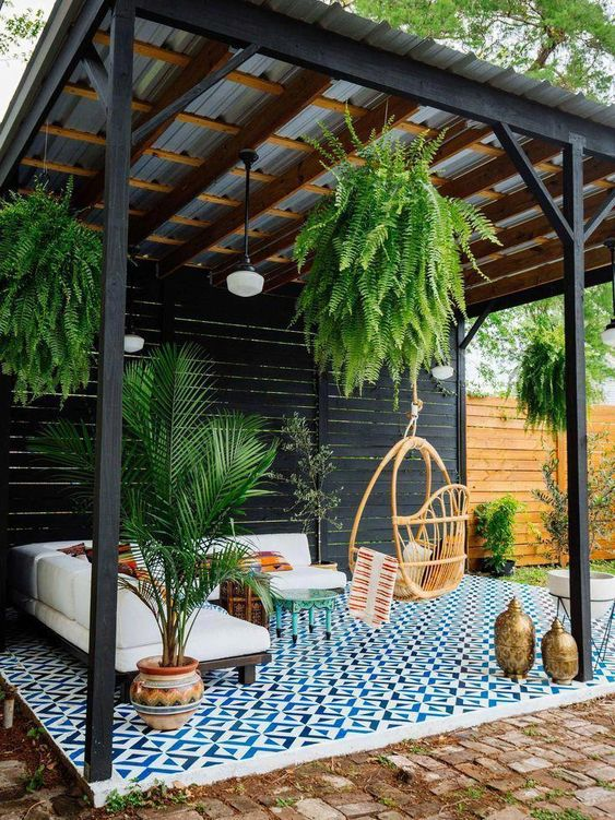 Pergola overhead outdoor couch, plants, and hanging chair