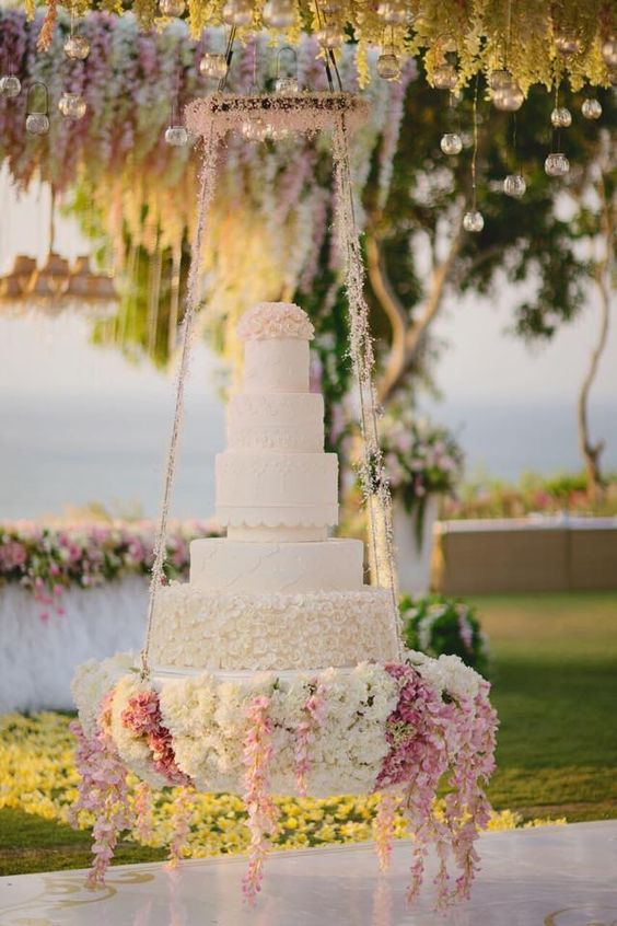 A suspended tiered wedding cake adorned with flowers // Pastel floral wedding decor inspiration: