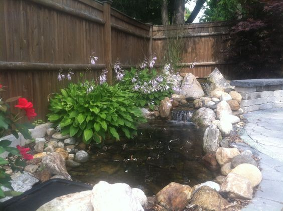 Waterfall meets up to paver patio with landscaping by Bahler Brothers in CT