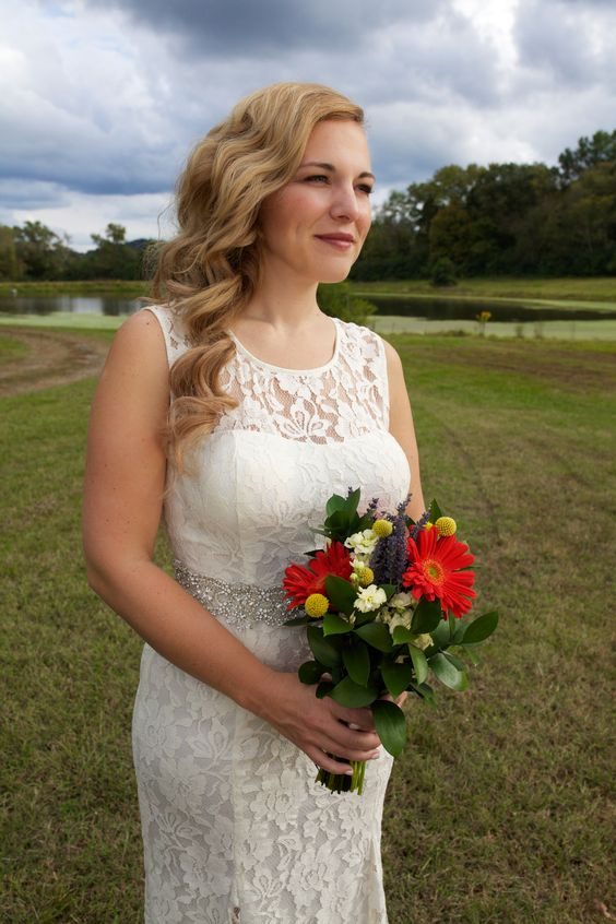 Soft makeup and relaxed side-swept curls are a lovey look for your wedding day.  Hair | Lacey West, Makeup | Brenlynn Craker, Photo Credit | Alicia Katy Photography