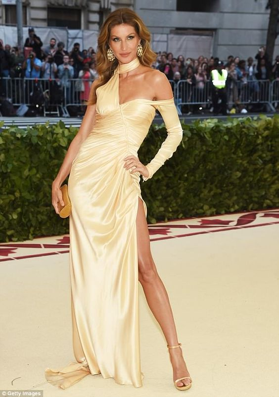 Stunner: Gisele arrived in a stunning gold Versace gown to the Met Gala on Monday...