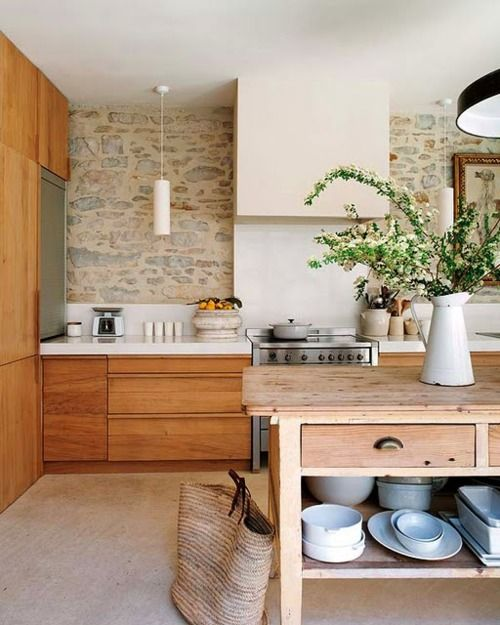 Kitchen - wood cabinets, white counters. sleek modern but earthy and soothing. stone wall, farm table as island