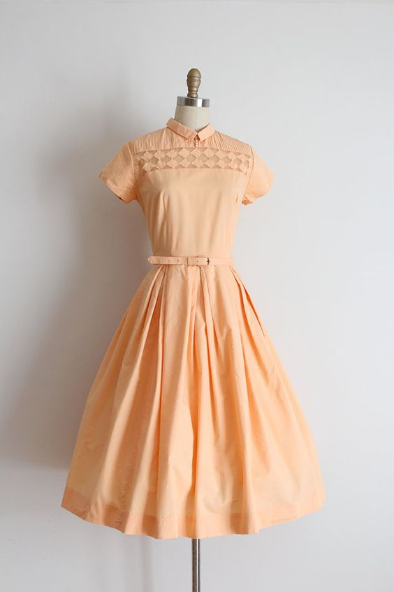 Super adorable peachy cotton day dress from the 1950s. This dress features a cute bodice with harlequin style cut out neckline detail, a fitted waistline with matching belt and an open skirt.: