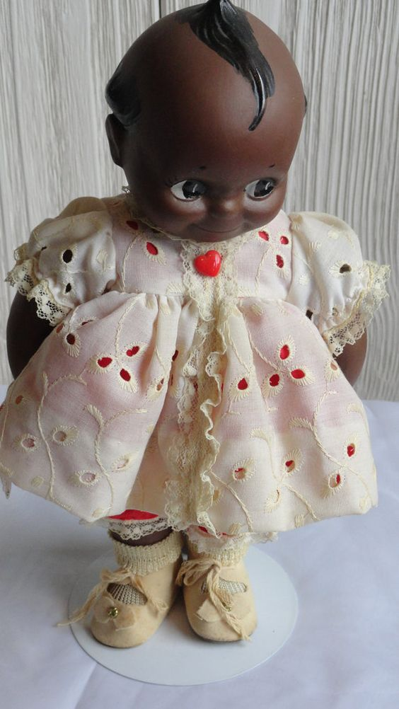 Adorable Vintage Black Kewpie Doll from the 1940s-1950s  In Exceptional Condition.  She is 12 Inches Tall, made of Bisque and has Fully Jointed Move-able Head, Arms and Legs.  She is Dressed In Red Knickers with White Lace and Has a Matching Red and White Eyelet Blouse.  Her Shoes are a Soft Tan with a Silver Toned Floral Decor Piece on the Top.  Does Come with Stand  ALL SHIPPING OVERAGES WILL BE REFUNDED THE DAY OF SHIPPING  8-130