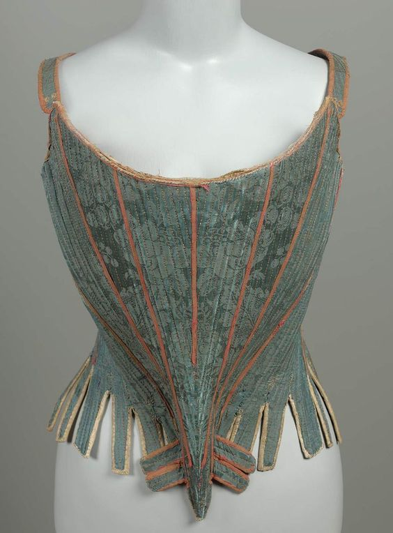 Stays, France, c. 1750. Blue silk damask in floral pattern; block printed cotton lining (brown floral pattern on ecru, similar to damask pattern). White kid tab binding and lining. Red silk tape over seams. Back lacing. Fully boned (whalebone).