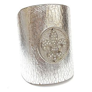 "This leather cuff is constructed of thick, resistant, genuine leather, has a snap closure feature, and is accented in a crystal-studded Fleur-de-lis matching the leather color. The cuff is adjustable for a desirable fit. Material: Genuine Leather - Size: 10"" Long x 3"" Wide - Color: Silver $39.99"