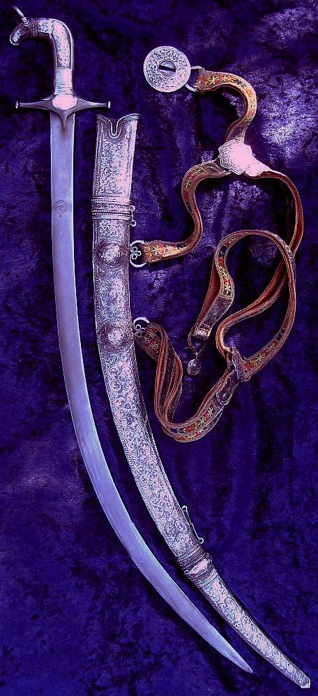 Persian shamshir, with silver scabbard, mounts, and sword belt from Hyderabad India, the scabbard is made in three pieces so that it can be taken apart for cleaning, the blade is 29 inches in a straight line, and 35 inches overall, with a kara khorassan type wootz steel blade.