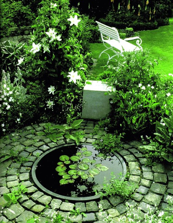 Small garden pond surrounded by a green and white garden. Beautiful backyards- love the way the pond is framed by the cobbles, makes it look much more interesting: