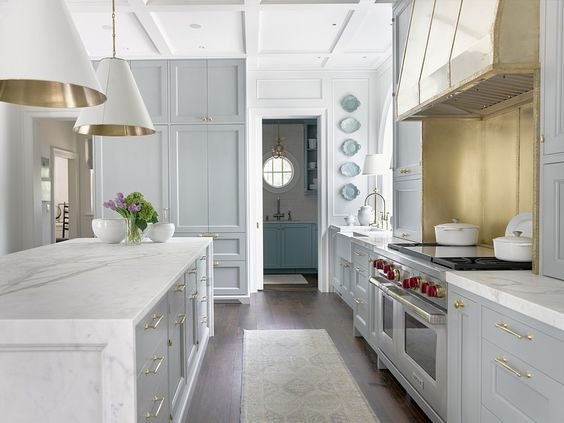 Traditional blue kitchen with pendants, brass hardware, plates, rug Shaker cabinetry.
