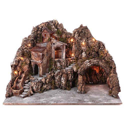 Borgo presepe illuminato con ruscello in movimento e grotta