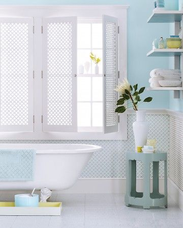 Here, washes of light sky blue on the walls and lots of white evoke the tranquillity of a tropical breeze. A pale aqua on the underside of the shelves extends the theme for anyone who's in the tub. Add another tropical touch by using radiator-grill panels on the walls and as shutters to provide privacy without sacrificing light.