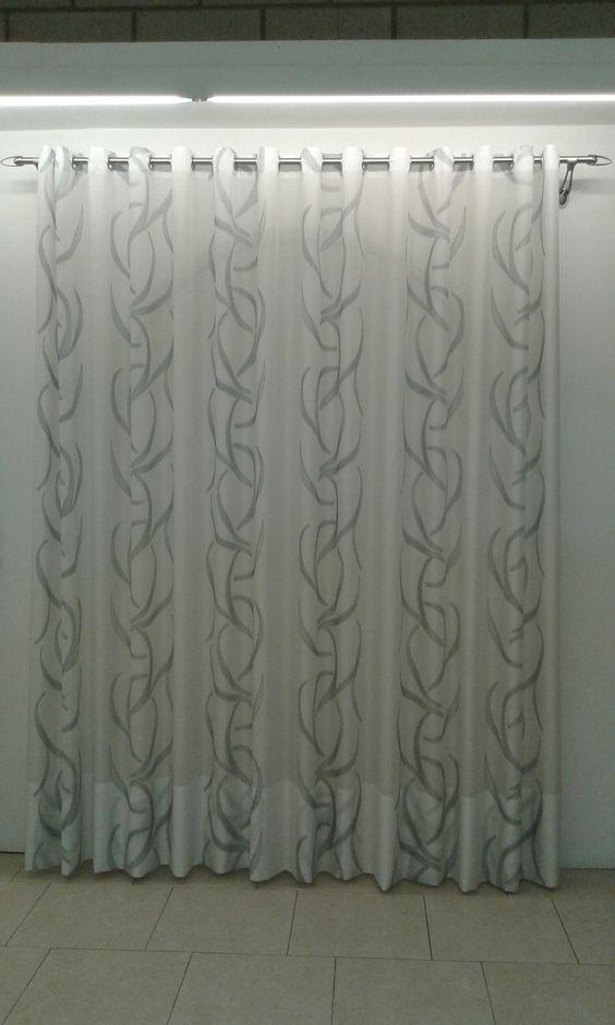 Tendaggio scorrevole manuale effetto onda mobida su bastone in acciao lucido con terminali e supporti satinati installato a parete, confezionato mediate inserimento di fettuccia con borchie su tessuto color bianco ottico con dettagli in argento lucido.