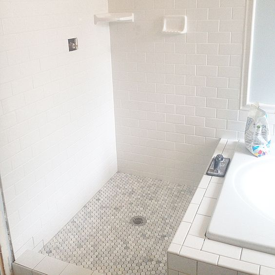 White Subway Tile Walls And Gray Hexagon Tile Flooring Is