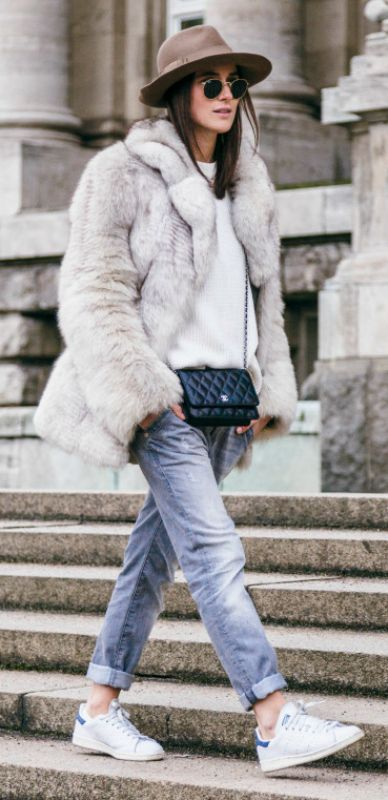 A big faux fur coat will add instant glamour to any look. Lena Lademann wears this classic white fur over a knit sweater and boyfriend jeans, an edgy every day look which is ideal for the winter season. Brands not specified.: