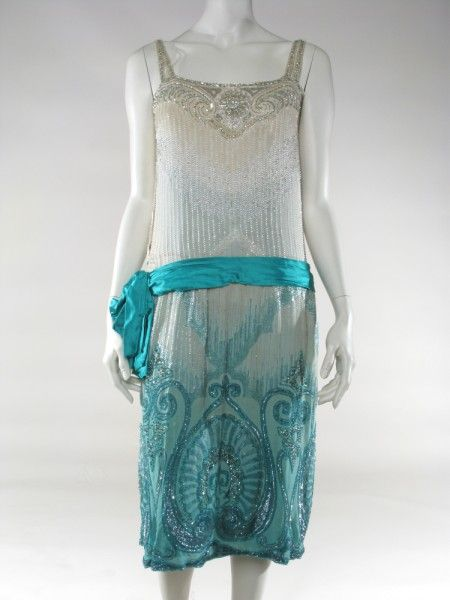 Beaded evening or 'flapper' dress. Off white sillk crepe, graduating to seagreen towards the hem; sleeveless with narrow shoulder straps, each in a cross-over style; dropped waist with turquoise green silk satin sash with made up bow to right side; whole dress decorated with elaborate geometric beaded design in silver, white and green bugle beads and sequin