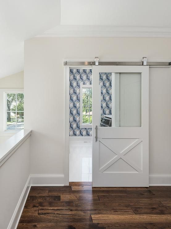 A Sliding Glass And White Wood Door Opens To A White And Blue Laundry Room Clad In White And Blue Patterned Wall Blue Laundry Rooms Wood Barn Door Laundry Room