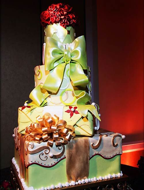 Four tier multi-coloured retro style cake made to look a parcel or gift box cakes. Decorated with a large green bow, bronze fondant ribbons and swirls with a red fondant flower wedding cake topper. From www.elegantcheesecakes.com           ........   #wedding #cake #birthday