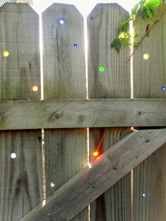 Holzzaun mit Löchern mit farbige Gläsern. Vielleicht kann man auch einfach Glasmurmeln in die Löcher stecken.