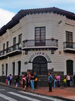 Quito Colonial hose of yellow brick with some people in the front