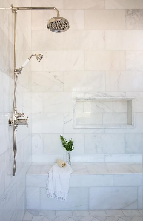 A Marble Tiled Shower Bench Is Positioned Beneath A Marble Tiled Niche Lined With Marble Pencil Til Marble Shower Tile Bathroom Shower Tile Shower Tile Designs