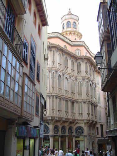 Can Corbella. Palma. Sobre una cornisa se eleva la fachada de tres plantas. Fachada ondulada y construida totalmente de madera. Ofrece una sucesión de ventanas con persianas curvas enmarcadas por pilares.