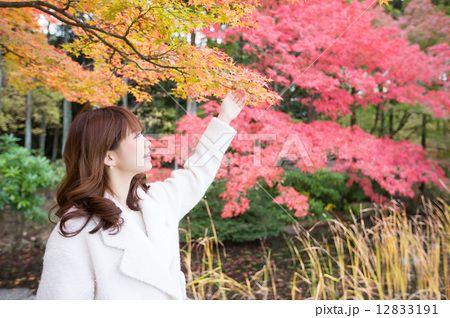 紅葉を背景にする笑顔の若い女性