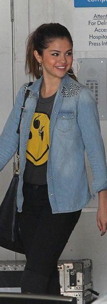 Who made Selena Gomez's smiley face top, black handbag and denim studded long sleeve top?