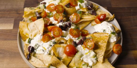 Greek Nachos I would make the yogurt/cheese and layer Greek salad ingredients and then use it like a surprise dip with chips.