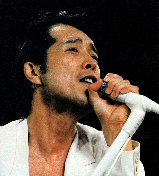 白いジャケットを着て歌っている若い頃の矢沢永吉の画像