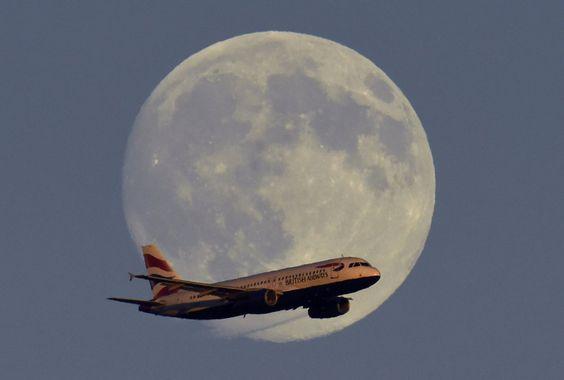 Un avión de pasajeros de British Airways pasa por delante de la luna en su trayecto hacia el aeropuerto de Heathrow, en Londres.