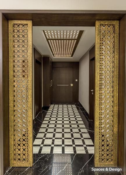 A wood and gold inspired entrance with intricate jali work for Foyer designs flats