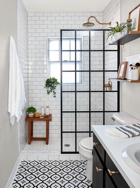 This DIY bathroom remodel features a doorless shower, redone tile, and a gorgeous black and white theme. #remodel #bathroomideas #blackandwhitebathroom #diy #bhg