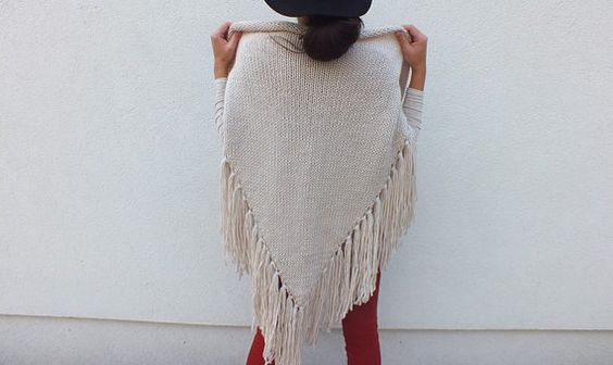 Gorgeous knitted triangle scarf with fringe trimming all around. Wrap is around your neck, or around your shoulders to wear like a poncho scarf.
