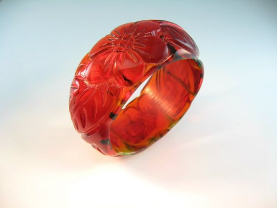 Chunky carved Lucite bangle is a luscious mix of translucent cherry red and apple juice with wispy splotches of yellow and green. The reddish